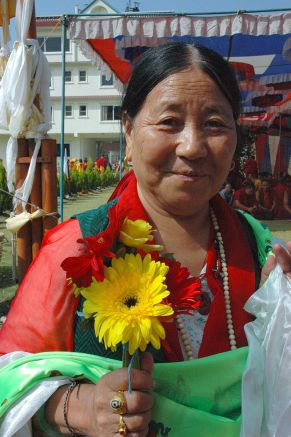 tibetan_woman_with_flower_and_katag_offerings_wearing_a_dzi_stone_ring_memorial_wrist_bracelet_to_tibetan_prisoners_and_mala_tharlam_monastery_courtyard_boudha_kathmandu_nepal